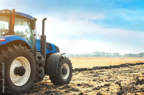 Wall mural Modern tractor working in a field.