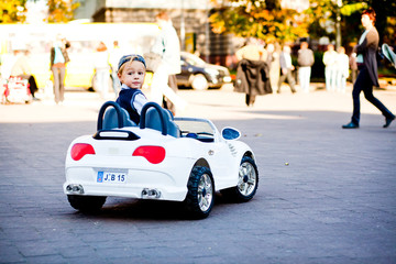 Hey, what is there? Cute little boy drives his first car