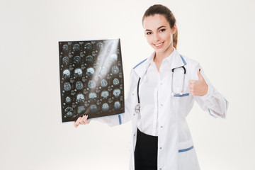 Happy young woman doctor holding radiography and showing thumbs up