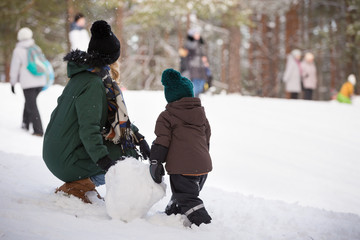 Cute little toddller boy and his mother playing with snow and making snowman. Child having fun outdoors in winter.