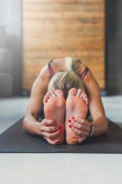 Woman makes yoga pose in class, sit forward bend asana