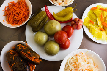 Pickled tomatoes and other vegetables in white bowls