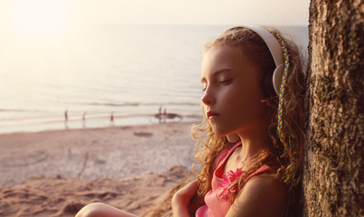 young girl listens to music on the beach