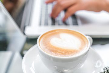Closeup of  Latte Coffee art and woman hand typing on laptop key