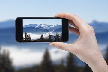 Hand taking picture of mountain peaks with cell phone