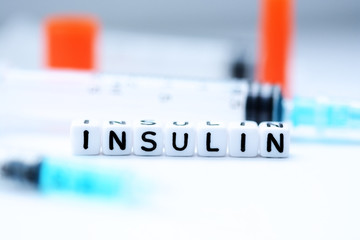 The word insulin spelled with plastic letter beads next to a syringe
