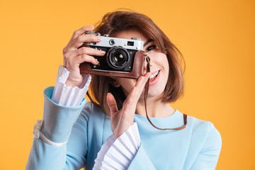 Portrait of smiling woman taking photos with old vintage camera