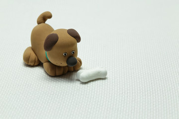 Dog from plasticine and a bone