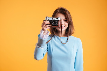 Cheerful woman standing and taking photos with old vintage camera