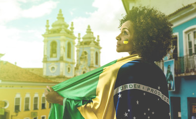Brazilian woman holding flag of Brazil in Bahia
