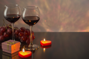 Valentines Day with a glass of red wine, grapes, gift, candles.