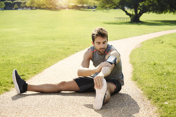 Athlete stretching in park on path