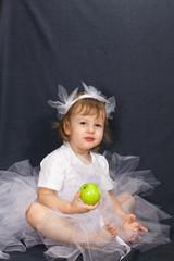 маленькая балерина сидит и ест яблоко