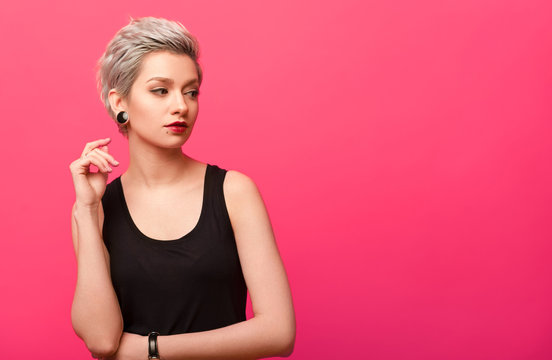 Girl with short blond dyed hair over pink background