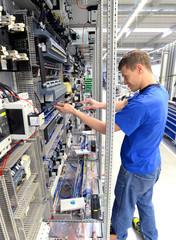 Montage von Elektronik in einer Fabrik - junger Mann arbeitet an einem Schaltschrank // Montage of electronics in a factory