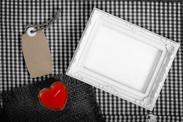 empty white frame next red heart sign from candle and paper tag