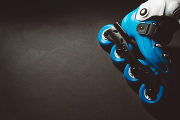 Close up view of blue roller skates inline skate or rollerblade on dark tinted grunge background