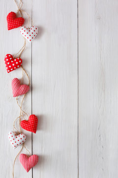 Valentine day background, pillow hearts border on wood, copy space