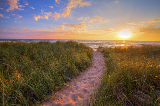 Path To A Summer Sunset Beach. Winding trail through dune grass leads to a sunset beach on the coast of the inland sea of Lake Michigan. Hoffmaster State Park. Muskegon, Michigan.
