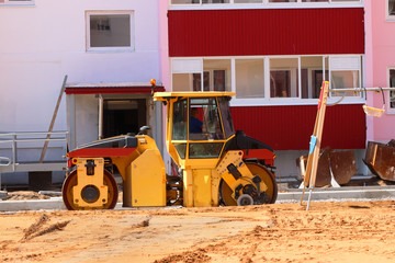 Big roller at construction site next to new building and playgro