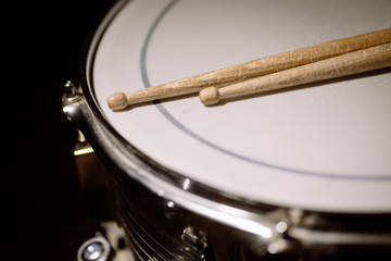 A snare drum and a pair of drum sticks.