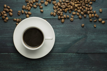 Coffee cup with grains and copyspace on dark texture