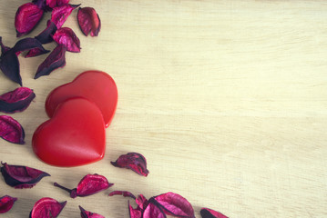 two gloss heart with dried flower on wood ground