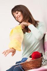 femme souriant qui tricote un pull jaune