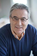 Smiling senior man with eyeglasses relaxing in armchair
