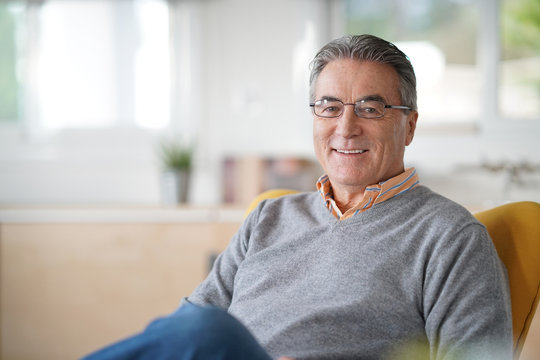 Smiling senior man with eyeglasses relaxing in armchair