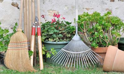 outils de jardinage et pots de fleurs dans un jardin