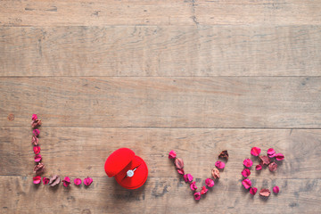 Caption word LOVE with engagement ring in red box on wood floor with copy space