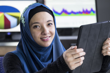 Young woman wearing a hijab using an ipad/tablet
