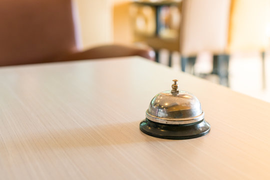 Concept hotel : old silver call bell on the wooden table, Hotel service bell on a table