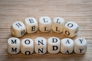 Hello monday text on a wooden cubes on a wooden table