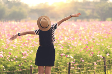 Beauty Girl Outdoors enjoying nature. Beautiful Teenage Model girl in black dress standing on the Spring Field, Sun Light. freedom concept