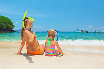 Happy family - mother with baby girl have fun in beach pool with sea surf. Travel healthy lifestyle, people water sport outdoor activity, swimming lessons and snorkeling on summer holidays with child