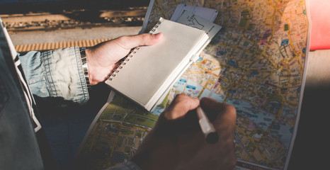 Hand closeup of young man traveler, backpacker at a map while planning for long vacation.