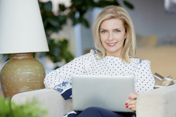 Working online. Shot of a beautiful mature woman typing on laptop while sitting at home and working online.