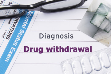 Diagnosis Drug Withdrawal. Medical notebook labeled Diagnosis Drug Withdrawal, psychiatric mental questionnaire and pills are on table in psychiatrist cabinet or counselor of this issue or problem