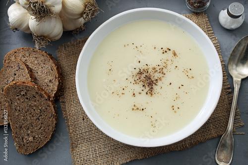 zuppa crema di aglio sfondo tavolo di cucina rustico\