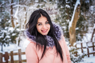 Brunette girl standing on the background of snow and trees and smiling