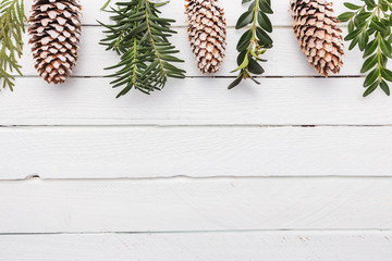 White wood Christmas border with snow covered pinecones