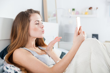 Young girl in bed taking selfie send kiss