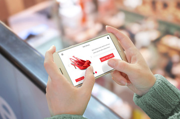 Shop with smart phone. Mobile in horizontal position in woman hand. Shopping center in background.