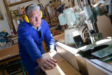 grey-haired carpenter using saw