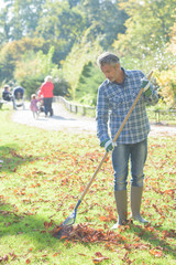 Man raking dead leaves