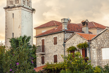 Old historical building facade with orange roof tiles in retro vintage style during sunset in old European town