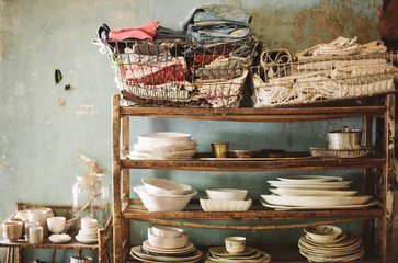 Rustic shelf with baskets of folded clothes and stacks of crockery