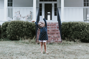 Girl dancing on grass in front of house